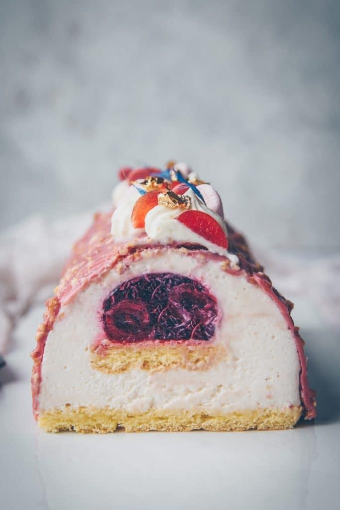 Buche avec une mousse au chocolat blanc vanillée, un insert à la cerise, un biscuit cuillère & un glaçage rocher rose - recette de ConfitBanane